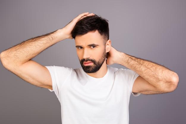 Ritratto di giovane uomo barbuto expertising i suoi capelli