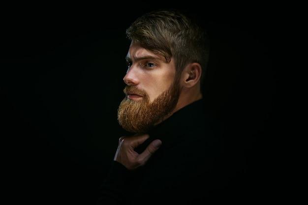 Ritratto di giovane uomo barbuto isolato su sfondo nero ragazzo con la barba premuroso, pensieroso, affascinante, in attesa hipster alla moda pensa al problem solving, trovando una soluzione
