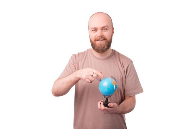Ritratto di giovane uomo barbuto che punta al globo, concetto di viaggio