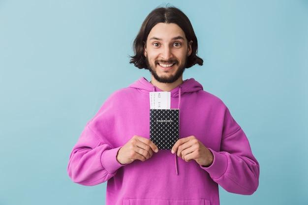 Ritratto di un giovane uomo barbuto che indossa abiti casual in piedi isolato sul muro, mostrando il passaporto con i biglietti aerei