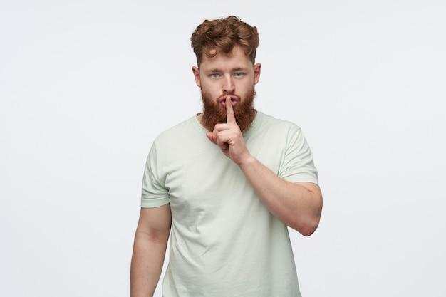 Ritratto di giovane uomo barbuto con i capelli rossi, indossa una maglietta vuota, si sente irritato e arrabbiato, mostrando il gesto del silenzio con un dito su bianco