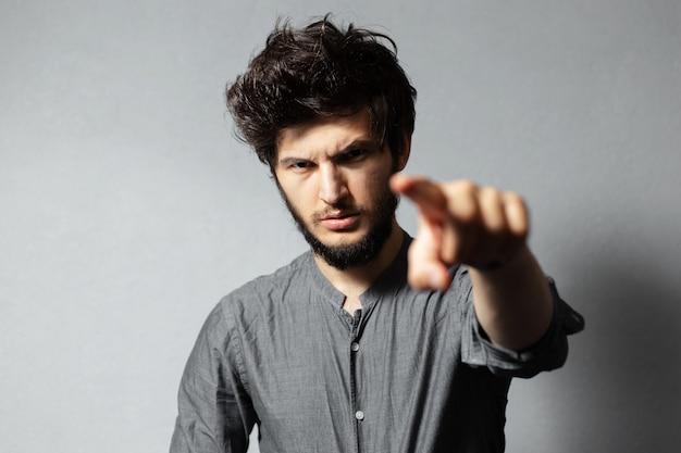Ritratto di giovane ragazzo barbuto e serio con i capelli arruffati, che punta con le dita verso la telecamera, su grigio.