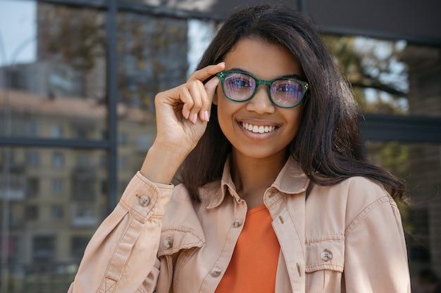 Ritratto di giovane bella donna afroamericana che indossa occhiali da vista, guardando la fotocamera