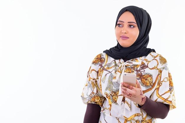 Ritratto di giovane bella donna musulmana africana che indossa l'hijab isolato contro il muro bianco
