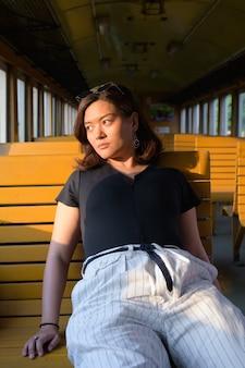 Ritratto di giovane bella donna turistica asiatica che guida il treno alla stazione ferroviaria di hua lamphong
