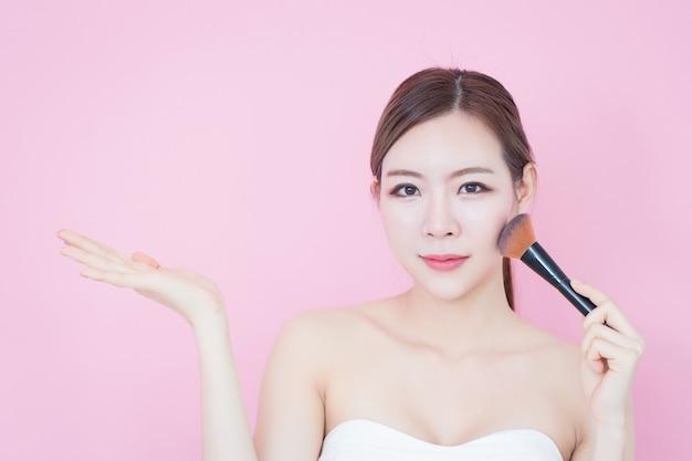Ritratto di giovane bella donna asiatica che applica polvere di pennello cosmetico che mostra spazio vuoto