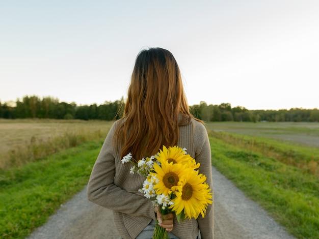 Ritratto di giovane bella donna asiatica nel campo di girasoli in fiore all'aperto
