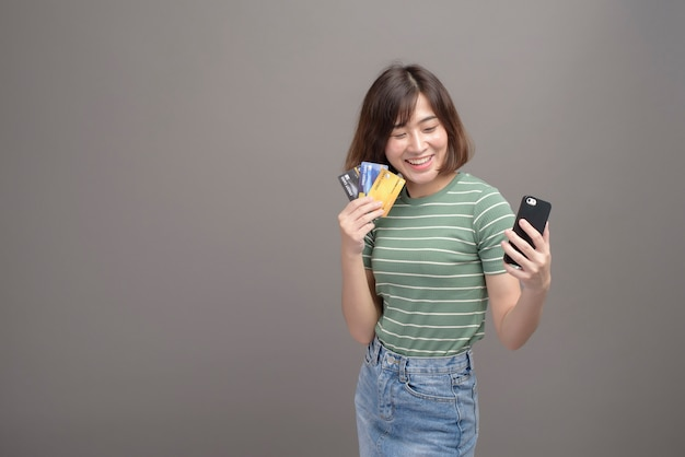 Un ritratto di giovane bella donna asiatica che tiene la carta di credito e lo smartphone isolato su grigio