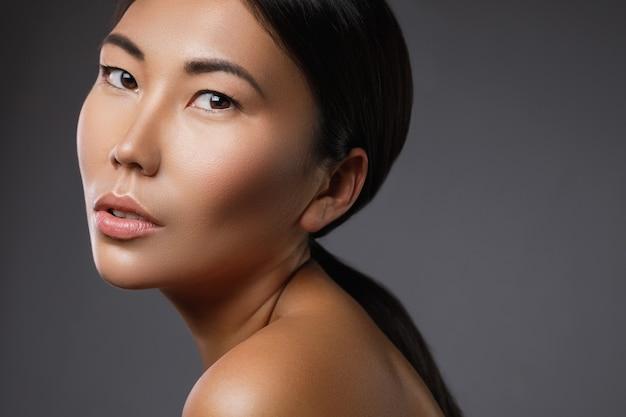 Ritratto di giovane e bella donna asiatica modello sul muro grigio