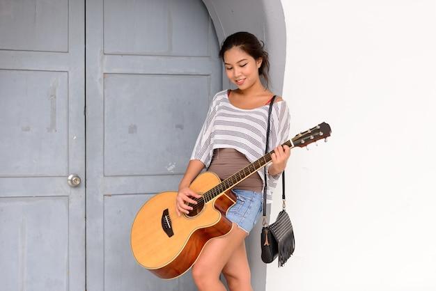 Ritratto di giovane bella donna asiatica, suonare la chitarra nelle strade della città all'aperto