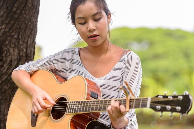 Ritratto di giovane bella donna asiatica, suonare la chitarra al parco all'aperto