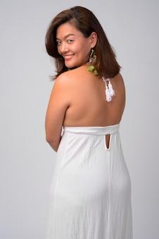 Ritratto di giovane bella donna asiatica pronta per l'estate contro il muro bianco