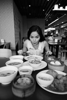 Ritratto di giovane bella donna asiatica che si rilassa alla caffetteria