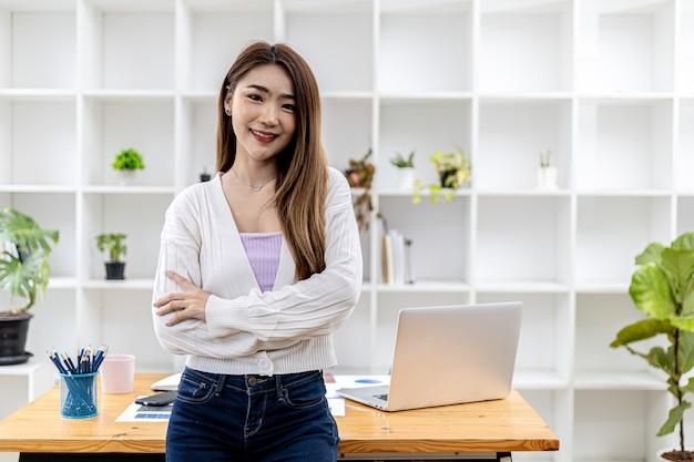 Ritratto di una giovane bella donna asiatica in piedi in una stanza bianca dell'ufficio, immagine concettuale di donna d'affari asiatica, moderna dirigente femminile, donna d'affari startup, donna leader d'affari.