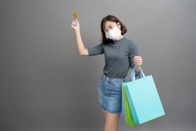 Un ritratto di giovane bella donna asiatica che indossa un mak chirurgico è in possesso di carta di credito e borsa della spesa colorata