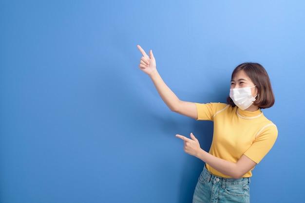 Un ritratto di giovane bella donna asiatica che indossa una mascherina chirurgica sopra, pandemia covid19 e inquinamento atmosferico (pm2