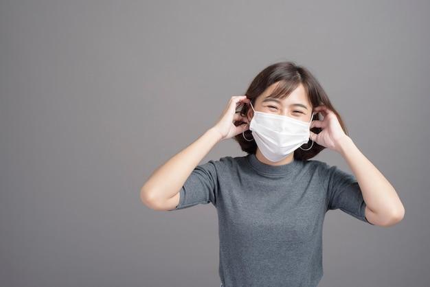 Un ritratto di giovane bella donna asiatica che indossa una mascherina chirurgica, pandemia covid19 e inquinamento atmosferico