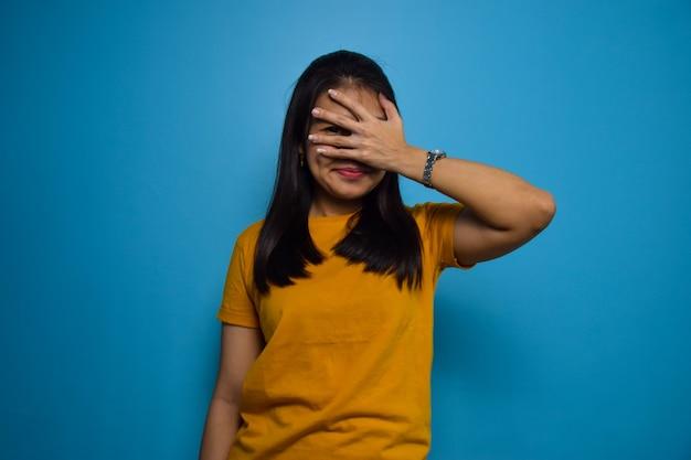 Ritratto di giovani belle donne asiatiche con sfondo blu isolato che copre il gesto degli occhi