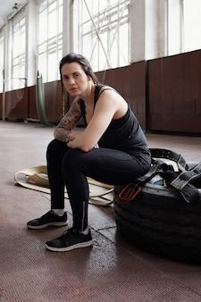 Ritratto di giovane bella donna atletica con braccio tatuato seduto sul pneumatico dopo allenamento cross training e alla ricerca