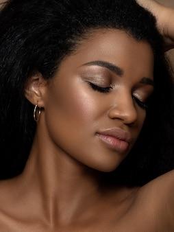 Ritratto di giovane bella donna nera che tocca i suoi capelli