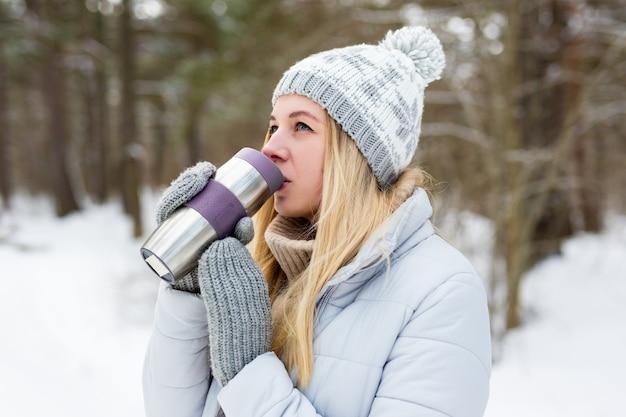Ritratto di giovane bella donna bionda che beve caffè nel parco invernale o nella foresta