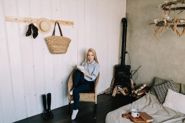 Ritratto di una giovane bella ragazza bionda a letto la mattina a casa in interni scandinavi buongiorno lifestyle