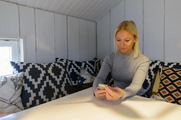 Ritratto di giovane bella donna bionda scandinava in un momento di relax a casa
