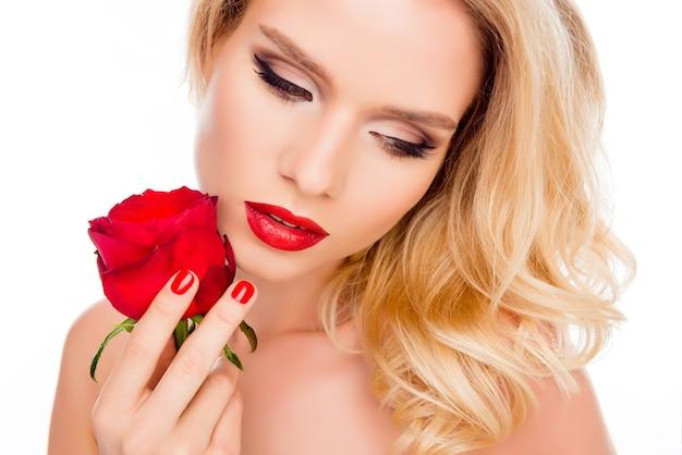 Ritratto di giovane bella donna bionda con gli occhi chiusi che tengono rosa rossa