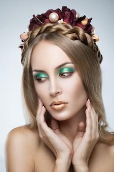Ritratto di giovane bella donna bionda con fiori nei capelli