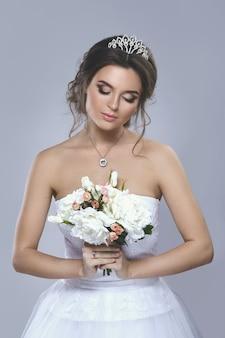 Ritratto di giovane bella sposa con bouquet di fiori