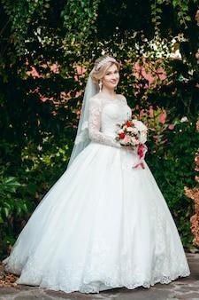 Ritratto di una giovane bella sposa con un bouquet