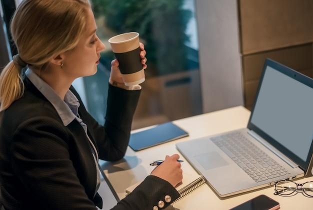 Ritratto di giovane bella donna di affari che gode del caffè mentre si lavora sul computer portatile