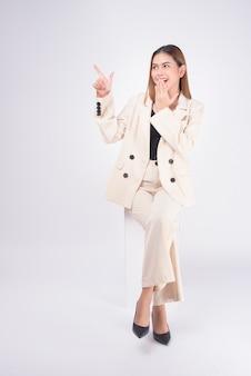 Ritratto di giovane bella donna di affari che porta vestito nello studio bianco del fondo.
