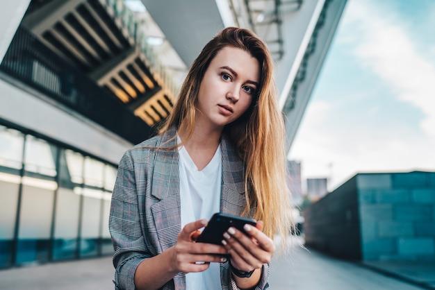 Ritratto di giovane bella donna d'affari vestita con indifferenza con lo smartphone nelle mani in posa davanti all'edificio in vetro high-tech del centro commerciale