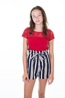 Il ritratto di giovane bella ragazza caucasica in maglietta rossa allegra nella foto dello studio ha isolato il fondo bianco
