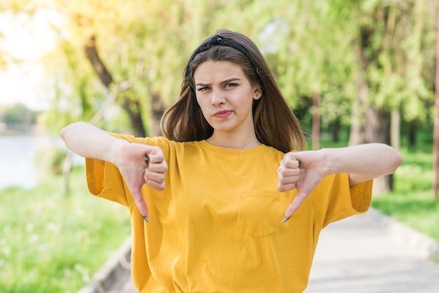 Ritratto di giovane e bella ragazza caucasica che mostra i pollici giù. non mi piace