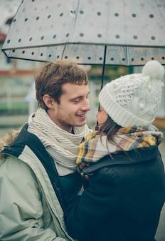 Ritratto di giovane bella coppia che si abbraccia sotto l'ombrellone in una giornata di pioggia autunnale. amore e concetto di relazioni di coppia.