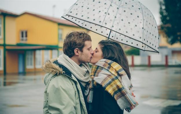 Ritratto di giovane bella coppia che si bacia sotto l'ombrellone in una giornata di pioggia autunnale. amore e concetto di relazioni di coppia.