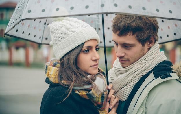 Ritratto di giovane bella coppia innamorata guardando sotto l'ombrellone in una giornata di pioggia autunnale. amore e concetto di relazioni di coppia.