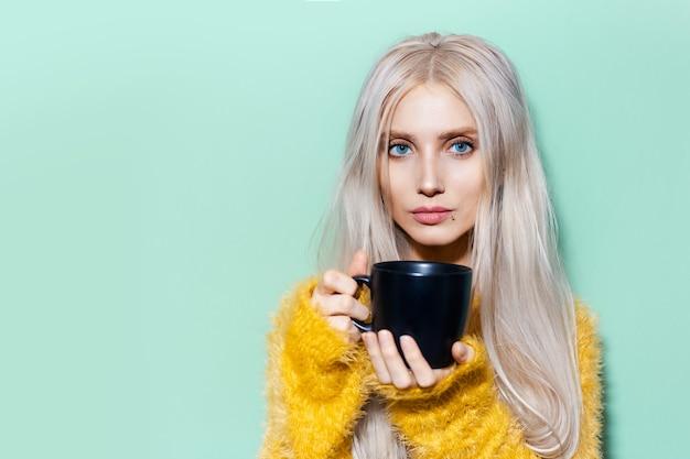 Ritratto di giovane bella ragazza carina con gli occhi azzurri, che tiene in mano una tazza di ceramica nera su uno sfondo di colore verde pastello con spazio per le copie. indossa un maglione giallo.