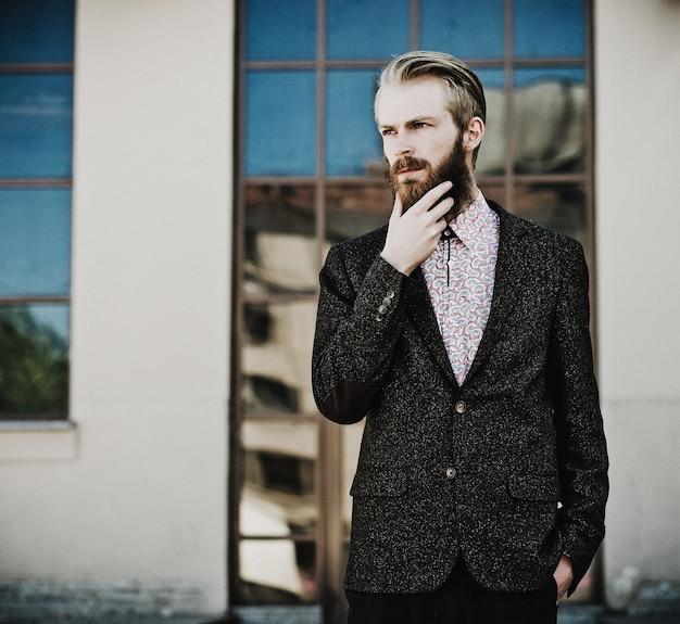 Ritratto di giovane bello uomo alla moda all'aperto