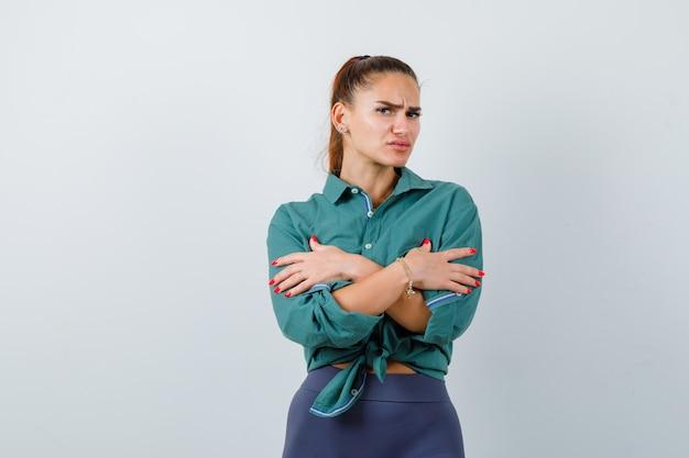 Ritratto di giovane bella donna che si sente fredda in camicia verde e sembra triste vista frontale