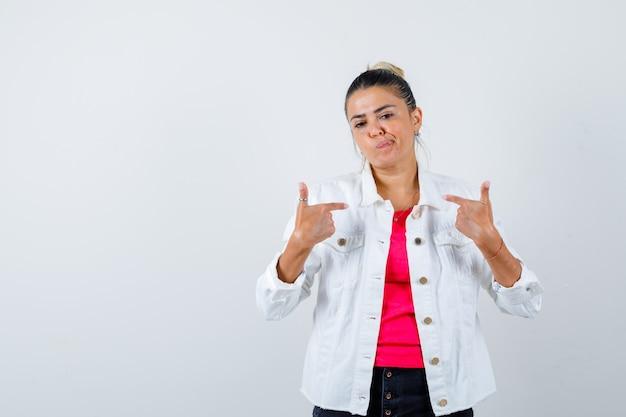 Ritratto di giovane bella donna che indica se stessa mentre incurva le labbra in maglietta, giacca bianca e guarda confusa vista frontale
