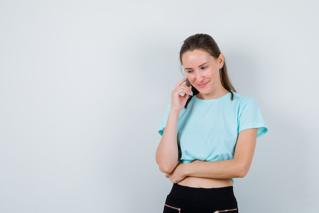 Ritratto di giovane bella donna che tocca la pelle del viso con le dita, guardando in basso in maglietta e guardando allegra vista frontale
