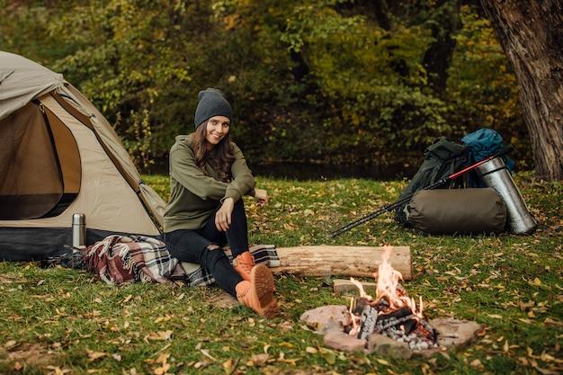 Ritratto di giovane bella turista femminile seduta sul tronco nella foresta vicino alla tenda e al sacco a pelo