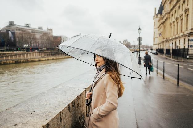 Ritratto di giovane bella ragazza che si nasconde sotto un ombrello da una piccola pioggia.