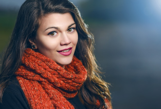Ritratto di una giovane bella ragazza in sciarpa lavorata a maglia rossa, sera all'aperto. la luce blu illumina il modello. tonalità fredde