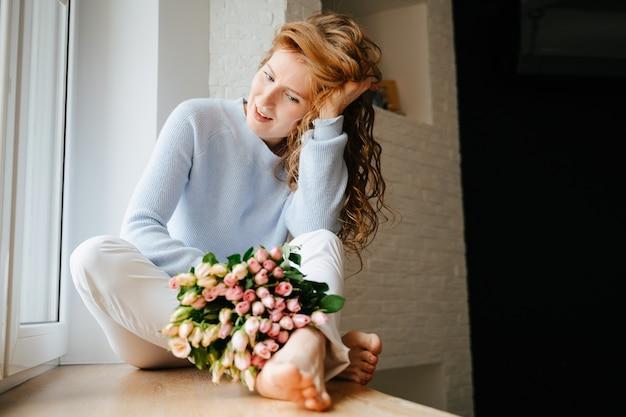 Ritratto di una giovane bella ragazza con un mazzo di rose vicino alla finestra. capelli rossi fluenti e ricci.