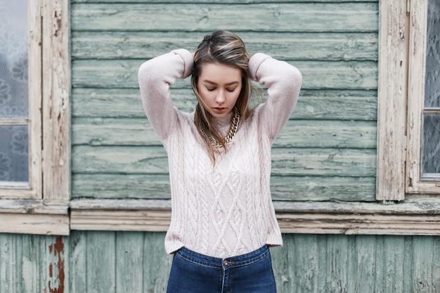 Ritratto di una giovane bella ragazza con il maglione rosa
