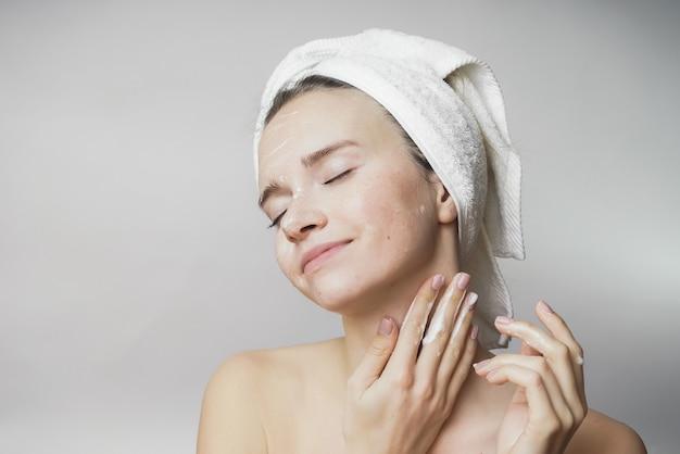 Ritratto di una giovane bella ragazza con un asciugamano in testa dopo una tazza di tè. ha chiuso gli occhi, spalma felicemente la crema sulla sua pelle